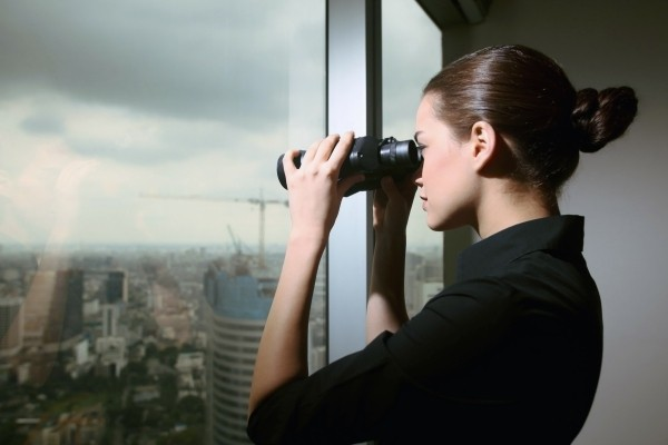 Business woman searching with binos through a large window for How To Get Quality Blog Content