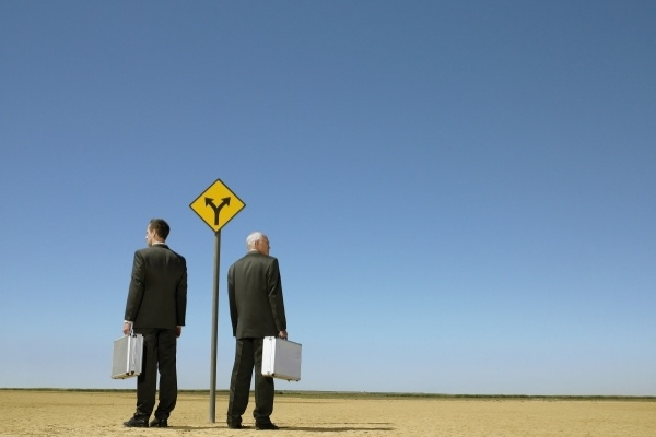 2 man in suits stand at a crossroads
