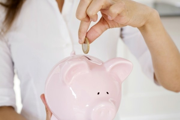 a lady putting money in a pink piggy bank for their blogging journey