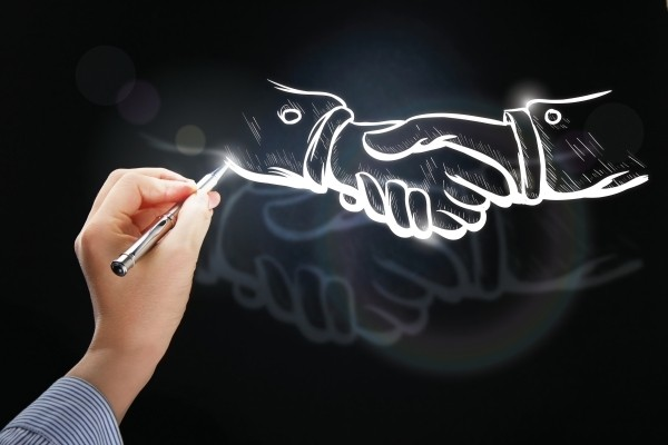 an artist drawing two hands shaking hands