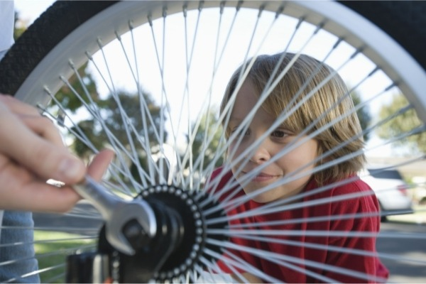 child looking through the spokes and wheels of a bicycle wheel