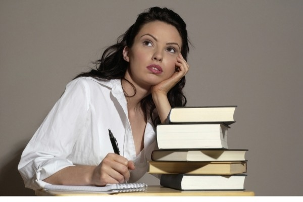 starting a blog - a writer next to a big pile of books